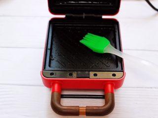 明目养肝的草莓酸奶三明治,三明治机器连接电源,把上下的烤盘刷上少许食用油。