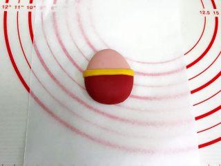 小福猪中国结馒头,贴合部分刷清水,取一根黄色长条面片粘在红色面皮的上方。