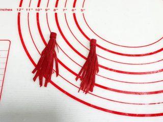 小福猪中国结馒头,如图上卷起来,取少量红色面团擀开切成约0.8厘米的长条状,贴合至顶部流苏接口处。