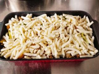 什锦咖喱焗饭,把炒好的米饭铺在容器中。在米饭上面。铺上一层奶酪丝。一定要铺均匀。
