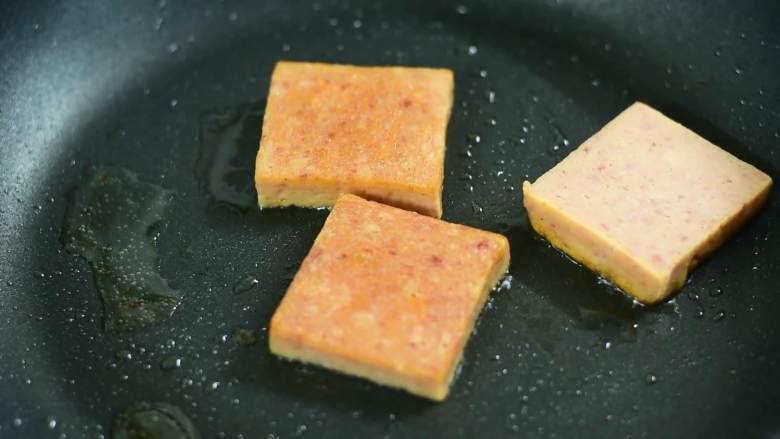 吃了这碗黯然销魂面,你一定会流泪(其实是辣哭的),锅中底油放入午餐肉,中火煎至两面金黄。