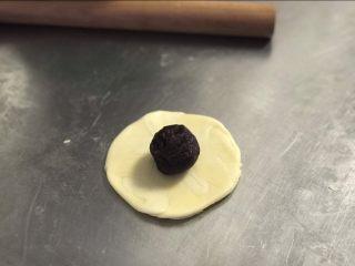 白皮酥,将面团按扁,檊开,不要檊太多,放入一颗馅料。