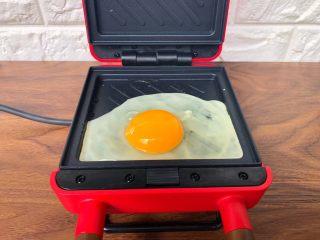 快手三明治,再打入鸡蛋,盖上盖子烤3分钟,烤好以后,把鸡蛋夹出来待用。