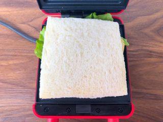 快手三明治,现在开始制作三明治,首先放入一片吐司,再放上一片生菜,再放上鸡蛋、香肠、芝士片,然后再放上一片吐司,盖上盖子,烤3分钟。