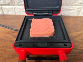 快手三明治,机器预热好以后,用刷子在烤盘里刷少许油,不要刷太多,一点点就可以,然后把香肠放入,盖上盖子烤2分钟,烤好把香肠夹出来待用。