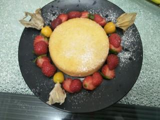 水果伴蛋糕,将蛋糕放入盘中,周边围上草莓,再放几颗菇娘果,洒上糖粉,再放几片薄荷叶做装饰即可。