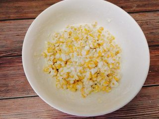 黄金玉米烙,将糯米粉,玉米淀粉和玉米粒混合,加入牛奶,将玉米粒混合至表面可以裹上面粉,为糊状,这样煎出来不会散。