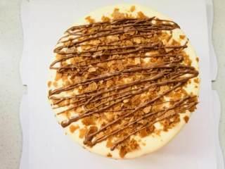爆浆海盐红丝绒奶盖蛋糕,表面撒上黄油脆片,挤上软化的巧克力。完成。