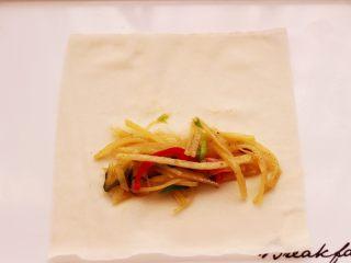 土豆丝红椒煎春卷,取一张春卷皮,放入炒好土豆丝。