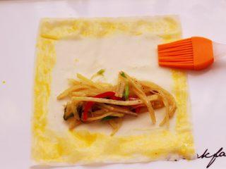土豆丝红椒煎春卷,春卷皮的四周,用刷子蘸少许鸡蛋液刷均匀。