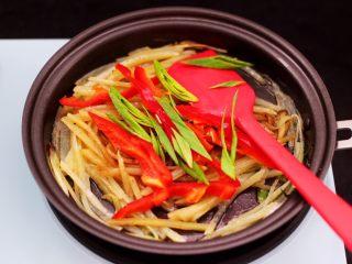 土豆丝红椒煎春卷,这个时候加入剩下的蒜苗和红椒丝。