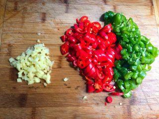 辣炒溪鱼干,青红辣椒清洗干净,切成圈圈待用,生姜去皮洗净,切成末待用。