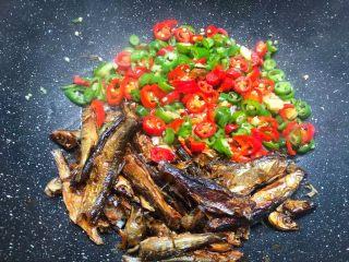 辣炒溪鱼干,溪鱼干炸好以后,把鱼干拨到一边,把生姜末和青红辣椒放入炒至断生。