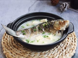 鲫鱼炖豆腐,食用之前在汤里放入少许的香菜末。