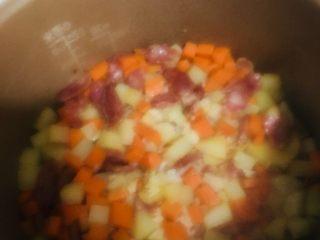 土豆香肠胡萝卜焖饭,待煮饭键跳起后再焖15分钟,再打开锅盖