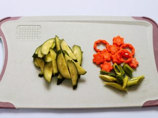 黄瓜虾仁什锦肉丸面,黄瓜洗净后用刀斜切成薄片,胡萝卜用模具刻成小花朵,蒜苗切碎备用。