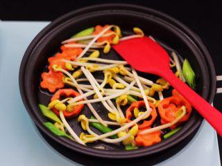 黄瓜虾仁什锦肉丸面,东菱早餐机的平底锅里倒入花生油烧热后,放入蒜苗和胡萝卜翻炒片刻后,再放入摘洗干净的黄豆芽继续翻炒。