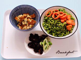 肉末豆干炒蒜苔,用刀把豆干切成小丁,蒜苔切碎,胡萝卜用模具刻花,木耳提前泡发好备用,葱姜切碎。