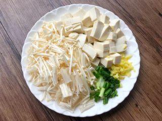 荠菜杂烩汤,把金针菇剪掉根部,清洗干净切成段,豆腐冲洗一下切成块,生姜去皮清洗干净切成末,葱去掉根部,清洗干净切成葱花。