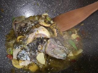 酸菜鱼🐠,锅中起油,葱爆香,放入腌菜翻炒,加入鱼头翻炒2分
