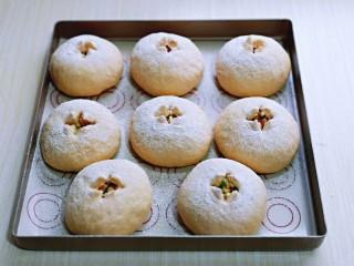 全麦熔岩芝士面包,取出发酵好的面包胚,是原来的1.5倍大,筛上一层高筋面粉,用剪刀剪十字口,把4个口角往外拉一下。