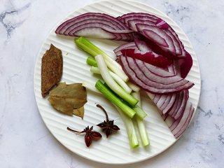 秘制蒜蓉酱,接着来准备配料,洋葱洗净后切片,香葱取葱白部分,去根后洗净,切成小段,八角、桂皮、香叶准备好,全部装入盘子里备用。