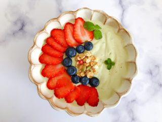 卡乐比牛油果香蕉慕斯雪,将之前备用的草莓,蓝莓如图所示摆放在表面,再随意撒上少许卡乐比,最后再用薄荷叶加以点缀装饰,我们的这一份颜值爆表的卡乐比牛油果香蕉慕斯雪就完成了