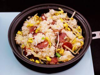 香肠豆芽炒饭,大火继续翻炒至所有的食材和米饭翻炒均匀。