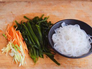肉末海带炒粉条,把焯过水的海带用清水冲洗一下后用刀切成丝,胡萝卜切丝,葱姜切丝,粉条沥干水分备用。