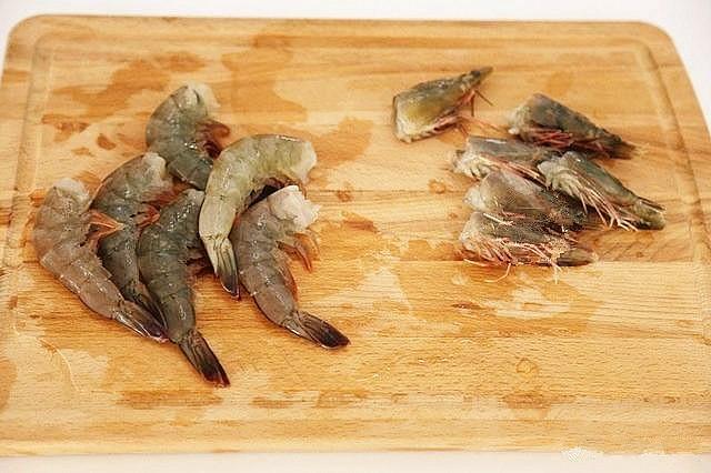 鲜虾粉丝煲,将虾清洗干净,去掉虾线,然后把一半儿虾的虾头和下身分开。另一半儿的虾要保留完整。