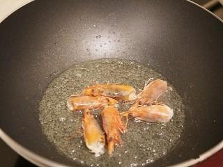 鲜虾粉丝煲,锅中倒入少许油,油热后,将虾头放入锅中煸炒出虾油,然后把虾头取出扔掉锅中留下虾油。