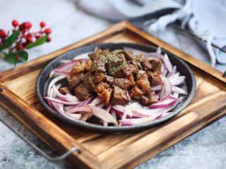 黑胡椒牛肉粒,将炒好了牛肉粒放在盛有洋葱的盘子里即可。 喜欢黑胡椒味道重一些,咸淡味重一些的可在表面再撒一些,也可以再撒些罗勒叶碎或者欧芹碎或者其它的香草碎,牛肉粒会更别具风味。
