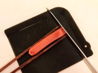 10分钟快手菜  肉粒多风味香肠炒俄式乳瓜,取一根小香肠,在香肠的两边各放一根筷子,把香肠切成连刀片