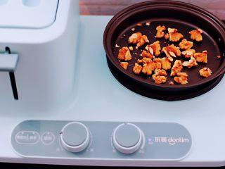 百合酒酿苹果核桃羹,启动东菱早餐机的煎锅,小火慢慢把核桃炒香后盛出备用。