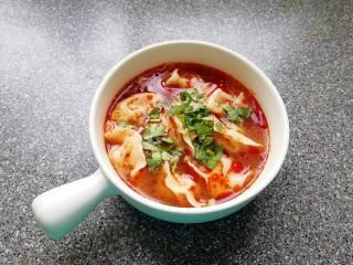 红油酸汤水饺,将饺子捞入碗中,加入两勺红油搅拌均匀,撒上香菜碎。