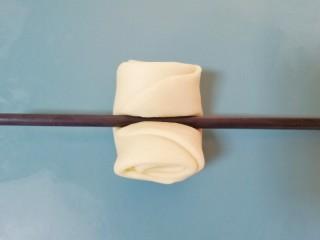 枣泥核桃卷,用筷子将松弛好的卷卷从中间压一下。