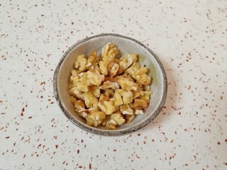 枣泥核桃卷,核桃仁烤熟以后趁热揉搓一下去皮(不用完全去掉),用刀切碎。