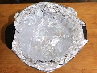 砂锅烤地瓜,用2张锡纸,错开、平铺在砂锅里面的小圆球上面。