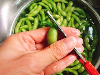 五香盐水毛豆,用剪刀将毛豆的头斜剪一刀,这样煮时更加入味