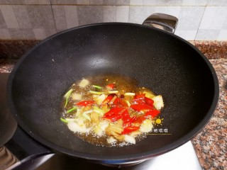 酸辣香酥带鱼,放入泡椒、泡姜、小葱、大蒜和1勺豆瓣酱翻炒出香味。