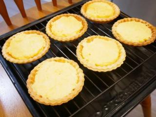 卡士达草莓塔,将卡士达内馅倒入塔皮将表面抹平,放进预热180度的烤箱烤约20分钟。