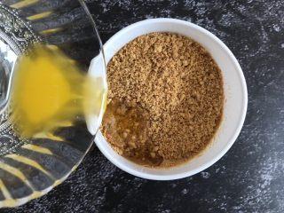 芒果慕斯蛋糕,将融化好的黄油倒入饼干末中,搅拌均匀