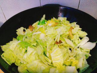 五花肉炒天津白,加入葱白段,姜片爆香,先倒入天津白帮,快速翻炒后再加入叶子。