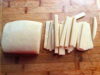 汤黄粿,首先把黄粿冲洗一下,先切成片,然后再改刀成条状,全部切好待用。