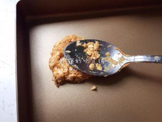 燕麦花生酱小小酥,取适量放烤盘上,用勺子背轻压整型。