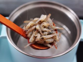 桃花虾爆韭菜,东菱早餐机的汤锅里,加入适量的清水烧开后,放入一勺盐后把洗净的桃花虾放入锅中。