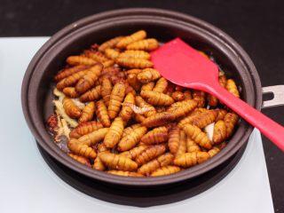 辣爆蚕蛹,把焯过水的葱蛹放入锅中大火进行翻炒。