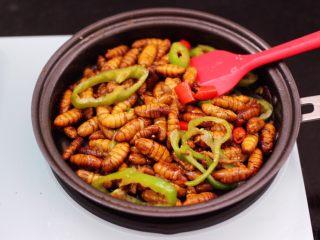辣爆蚕蛹,大火继续翻炒至青尖椒断生变色。
