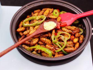 辣爆蚕蛹,加入鸡精调味提鲜。