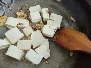 白菜炖豆腐粉条,倒入豆腐翻炒一下